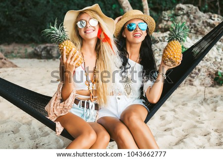 Two cute beautiful girls in bokho style dressed shirts shorts light cape bracelets necklaces, in the hair decorative colored feathers, straw hats, with pineapple in their hands sit in a hammock #1043662777