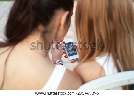 Two cute beautiful young women friends sitting on park bench on summer day, browsing pictures on smartphone, back view, focus on device screen #295469396