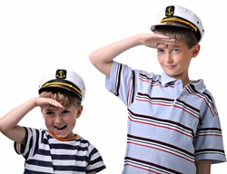 two cute boys dressed like a sailor, both in captain cap. isolated over white background.