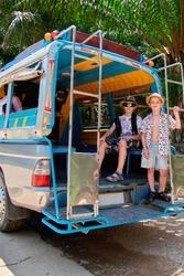 Two cute boys sit in the popular asian Tuk-Tuk taxi.