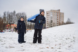 two cute caucasian boy standing on snowy slope in public city park holding a snow saucer. Image with selective focus