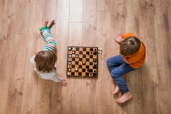 Two cute children playing chess at home or kindergarten. Table game. Preschool boy and girl play on the floor with educational toys. Toys for preschool and kindergarten. Top view.