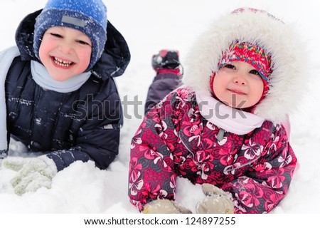 Two cute children playing on snow in winter time