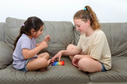 Two cute children playing with the Pop It fidget. One laughing girl raises hands in victory. Push pop bubble flexible fidget sensory toy provide discharge and are good for the development of kid.