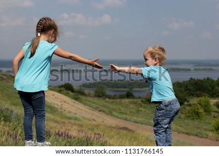 Two cute children, sister and brother, reaching towards each other by hands over beautiful landscape, help and support concept, friend and family, summer outdoor