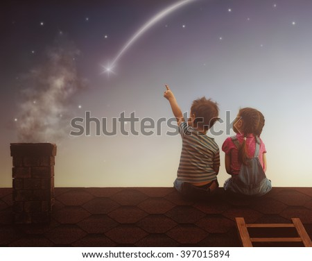 Shutterstock Two cute children sit on the roof and look at the stars. Boy and girl make a wish by seeing a shooting star.
