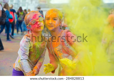 Two cute european sisters child girls celebrate Indian holi festival with colorful paint powder on faces and body