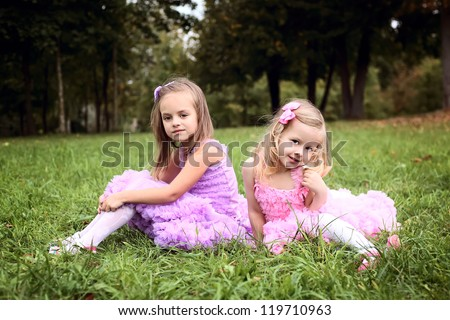two cute girlfriend in beautiful dresses are laughing in the summer park