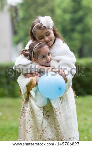 Two cute girls in ornate dress, aged 5 and 10, hugging and smiling. Outdoors