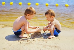 Two cute kids building sand castle on the beach