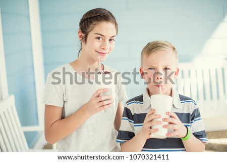 Two Cute kids drinking milkshakes or flavored drinks together outdoors on a warm summer day. Enjoying some cool liquid refreshment #1070321411