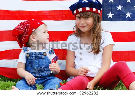 Two cute kids eating suckers next to an american flag