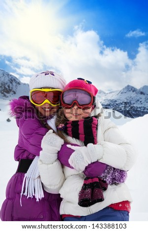 Two cute kids girls hugging together with mountain on background