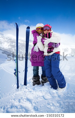 Two cute kids girls hugging with skis and mountain on background