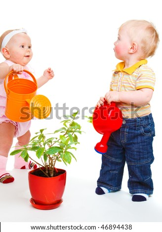 Two cute kids watering a plant