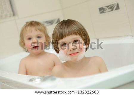 Two cute little boys having a bath together