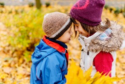 Two cute little children standing forehead to forehead in autumn park, happy cheerful kids brother with sister having fun together, side view