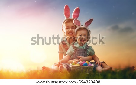 Two cute little children wearing bunny ears. Girls are sitting on the lawn. Kids with Easter eggs in the rays of the setting sun.
