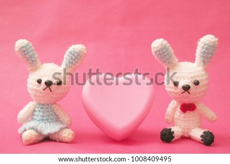 Two cute little crochet rabbit couple with pink heart on pastel background  #1008409495