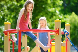 Two cute little girls having fun on a playground outdoors in summer. Sport activities for kids.