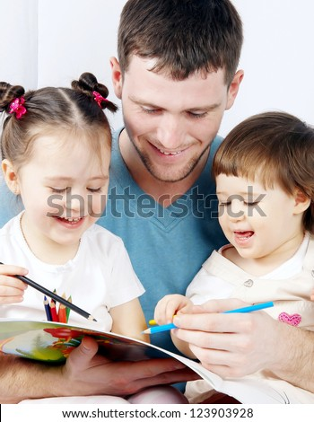 two cute little girls with their dad paint crayons