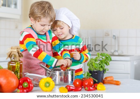 Two cute little kid boys cooking italian soup and meal with fresh vegetables in home\'s white kitchen. Sibling children in colorful shirts.