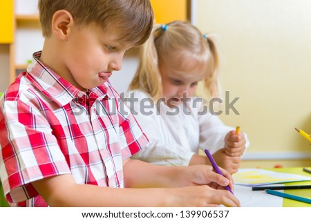 Two cute little preschool kids drawing with crayons at the table