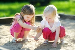 Two cute little sisters playing in a sandbox