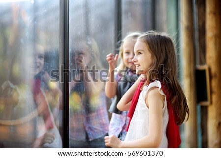 Two cute little sisters watching animals in the zoo on warm and sunny summer day. Children watching zoo animals through the window.