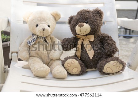 Two cute plush bears sitting on white seat and talking, eye contact, beige teddy bear and dark brown teddy bear, both with ribbon