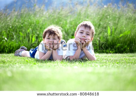 Two cute preschool siblings lying on green grass with field in background..