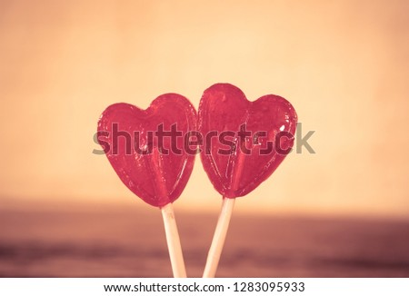 Two cute red heart shaped lollipops on rustic wooden table and beautiful romantic mood light and blur background as metaphor of love, togetherness and Valentines day greetings car design concept. #1283095933