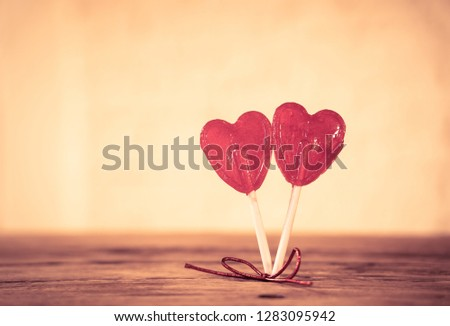 Two cute red heart shaped lollipops on rustic wooden table and beautiful romantic mood light and blur background as metaphor of love, togetherness and Valentines day greetings car design concept. #1283095942