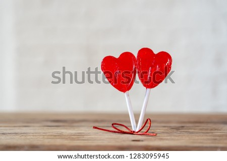 Two cute red heart shaped lollipops on rustic wooden table and beautiful romantic mood light and blur background as metaphor of love, togetherness and Valentines day greetings car design concept. #1283095945