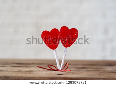Two cute red heart shaped lollipops on rustic wooden table and beautiful romantic mood light and blur background as metaphor of love, togetherness and Valentines day greetings car design concept. #1283095951
