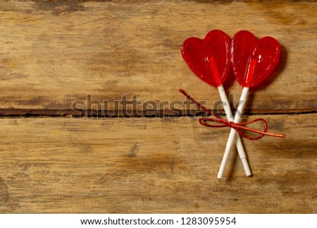 Two cute red heart shaped lollipops on rustic wooden table and beautiful romantic mood light and blur background as metaphor of love, togetherness and Valentines day greetings car design concept. #1283095954