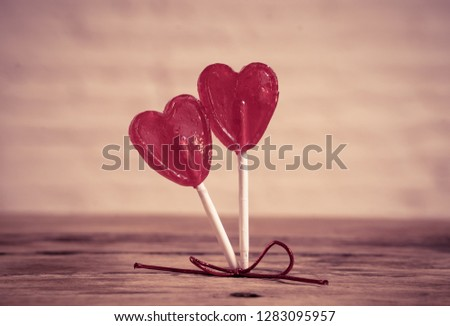 Two cute red heart shaped lollipops on rustic wooden table and beautiful romantic mood light and blur background as metaphor of love, togetherness and Valentines day greetings car design concept. #1283095957