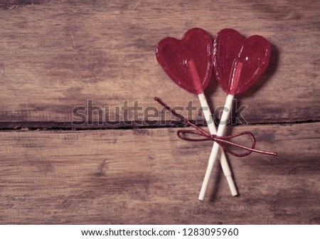 Two cute red heart shaped lollipops on rustic wooden table and beautiful romantic mood light and blur background as metaphor of love, togetherness and Valentines day greetings car design concept. #1283095960