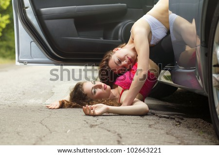 Two cute sexy young women lying on the road