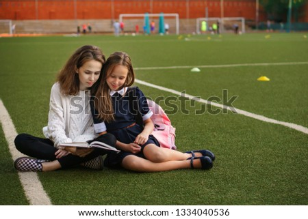 Two cute teen sisters read book while sitting on green lawn. Running track and football field in background. School stadium. Time together