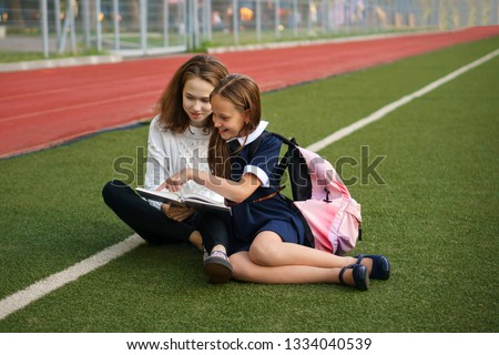 Two cute teen sisters read book while sitting on green lawn. Running track and football field in background. School stadium.