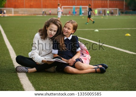 Two cute teen sisters read book while sitting on green lawn. Running track and football field in background. School stadium. Family time together