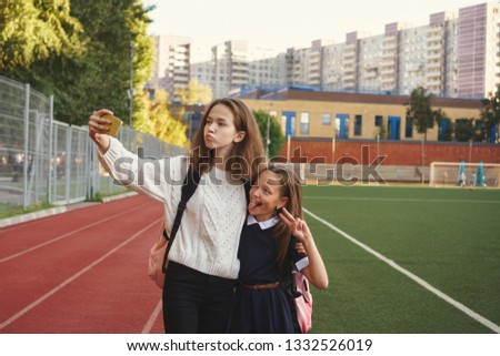 Two cute teen sisters take selfies and stand on playground. Older girl is holding cell phone and is hugging youngest by shoulders. Running track and football field in background. School stadium.