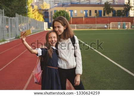 Two cute teen sisters take selfies and stand on playground. Youngest girl is holding cell phone. Running track and football field in background. School stadium.