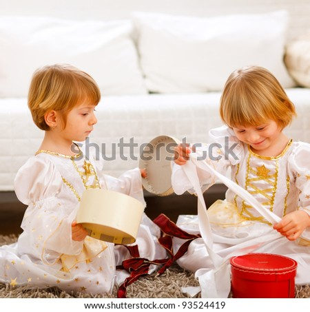 Two cute twins girls opening presents near Christmas tree - stock photo