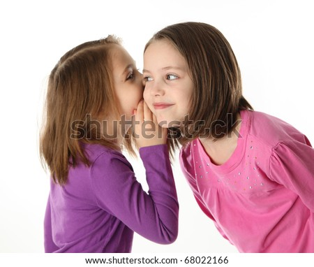 Two cute young sisters sharing a surprising secret, isolated on white - stock photo