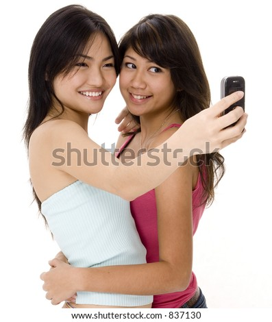 Two cute young women take their picture using a phone