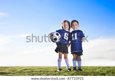 Two cute youth soccer players wearing their team uniforms