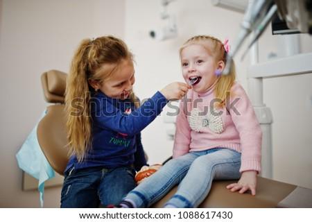 Two cutie little baby girls at dentist chair. Children dental.