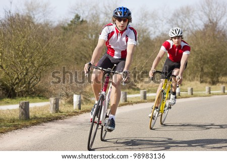 Two cyclists leaning inwards in the curve of a road during a training tour on a sunny spring day